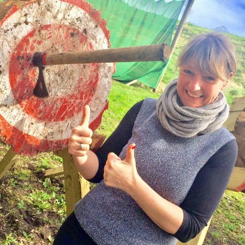 Girl smiling and posing with her axe target during Orangeworks fun outdoor activity.