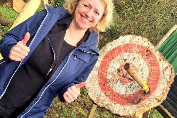 Delegate smiling with axe throwing target