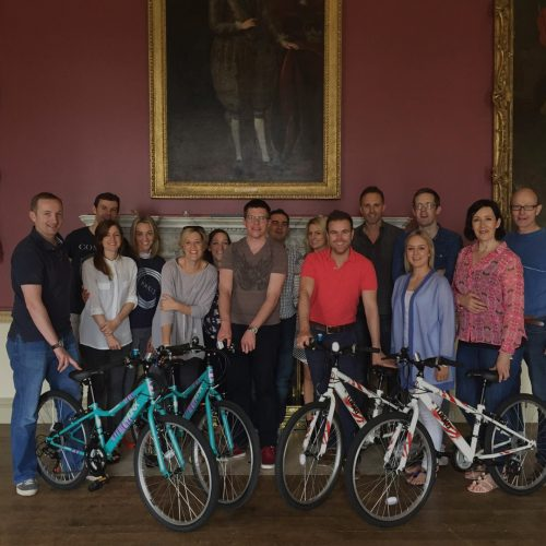 Group of delegates with the bikes they built during an Orangeworks team-building activity that gives back to the community.