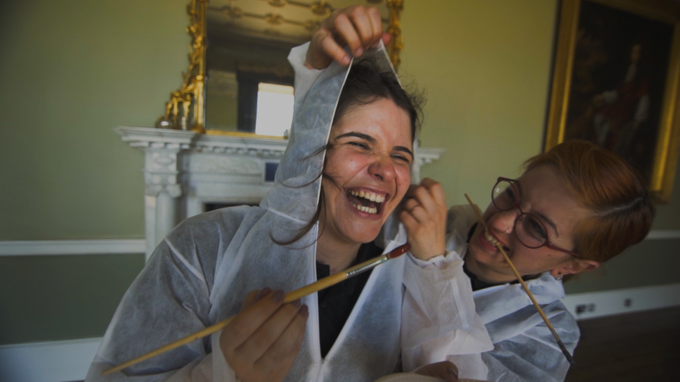 Two ladies laughing, holding paintbrushes. during the team bonding challenge called The Big Picture by Orangeworks.