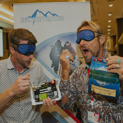 Delegates wearing blue blindfolds while tasting fake food which is a prop for Peak Performance, a team bonding experience.