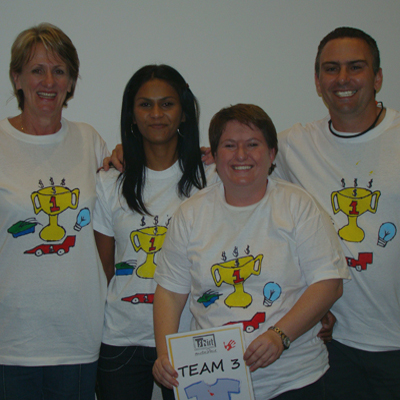 Team 3 smiling wearing their newly designed t-shirts