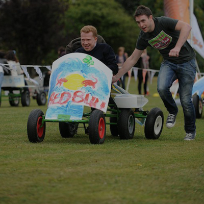 Delegates racing their Red bull decorated go-kart during Thunder Races, an outdoor team building game by Orangeworks.