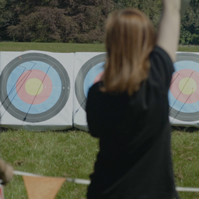 Back of delegate cheering after hitting the target during archery