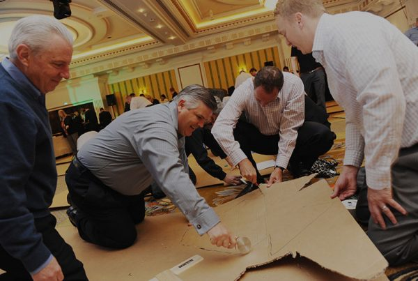 Happy delegates cutting the cardboard for their flat out team building event