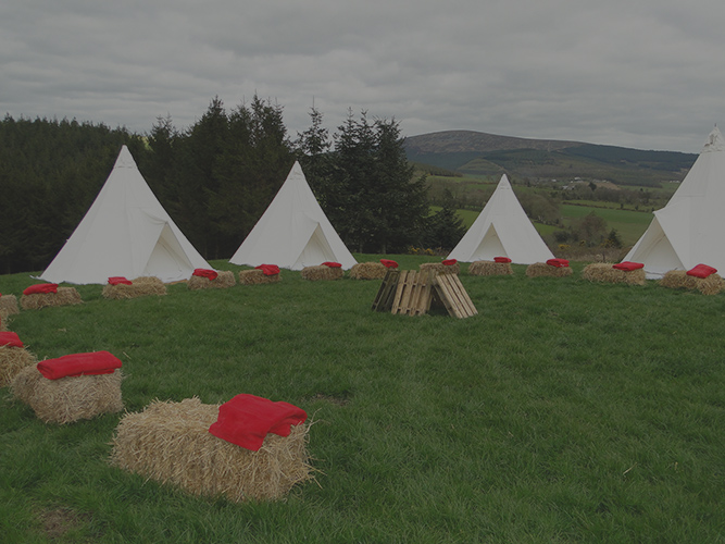 Bails of hay with red blankets on them and four teepee tents in a field, ready for Digital Detox.