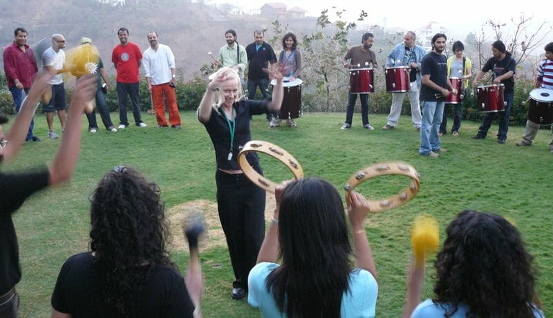 Delegates standing in a circle holding their instruments, following the instructor's guidelines during Revel Music.