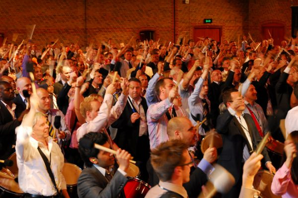 A corporate team with their hands in the air, enjoying the finale of Revel Music, one of Orangeworks team building activities