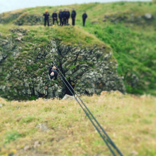 A delegate abseiling between two cliffs on a bespoke team building adventure with Orangeworks