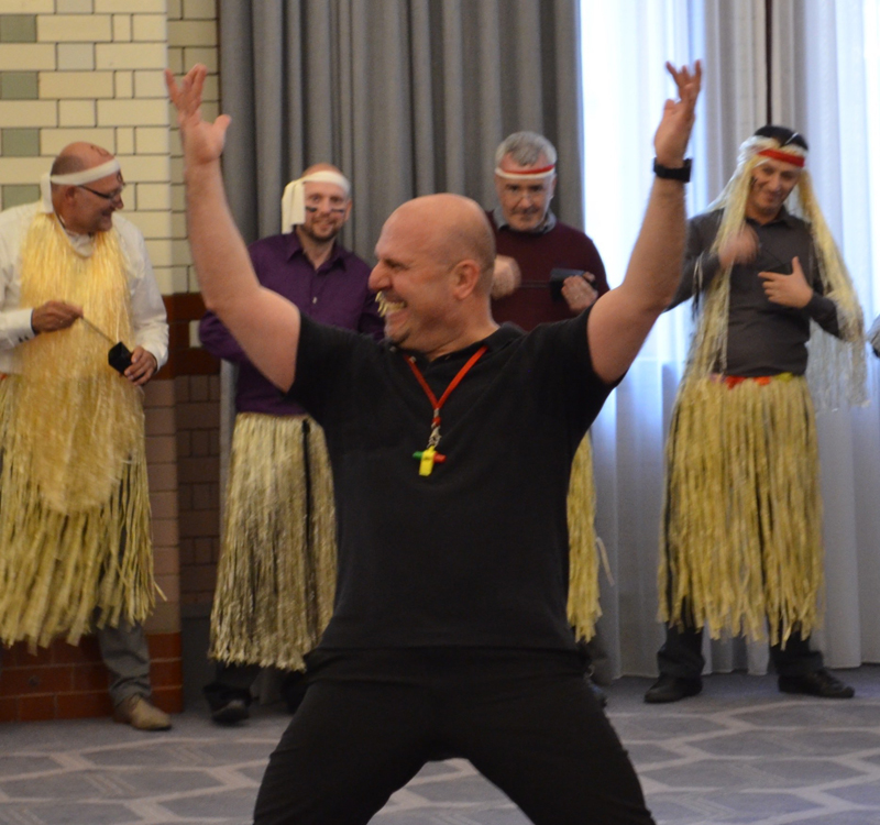 Ed Freitas, Orangeworks haka instructor, with his hands in the air, with delegates behind him wearing hula skirts.