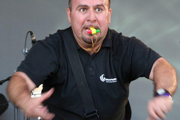 Ed Freitas, Orangeworks main haka instructor, with a whistle in his mouth while teaching delegates the haka.
