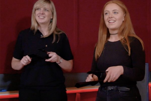 Two delegates standing with their instruments in their hands waiting for the Beat It Instructor to explain the team challenge