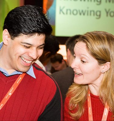 Two people wearing red jumpers chatting to each other during an icebreaker conference by Orangeworks called Knowing Me Knowing You.