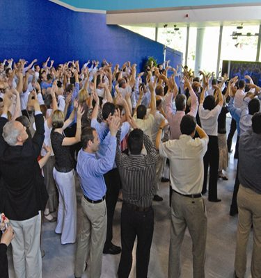 Delegates with their hands in the air singing & dancing during One Voice, a team-building energiser by Orangeworks.
