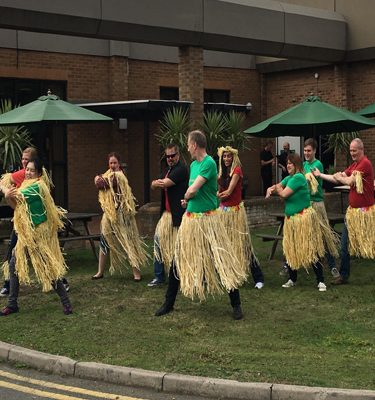 Team wearing straw hula skirts while learn to do the haka with Orangeworks