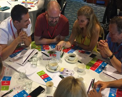 Delegates discussing their product innovation during Global Innovation Game, a fun team experience hosted by Orangeworks.