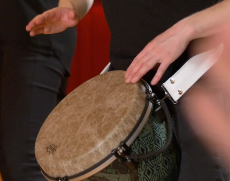 A man beating a drum with his hands during Global Grooves, a musicial team building activity by Orangeworks.