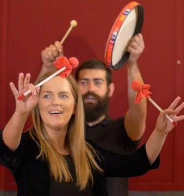 Two delegates smiling whilst raising hands in the air with instruments