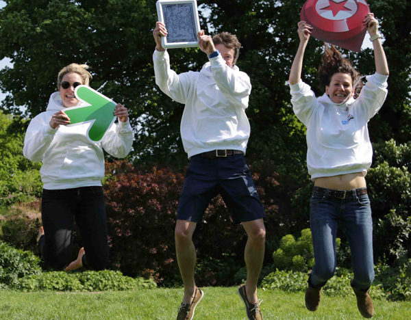 Happy team jumping in the air holding their iPad and signs as they completed the tablet based treasure hunt with Orangeworks.