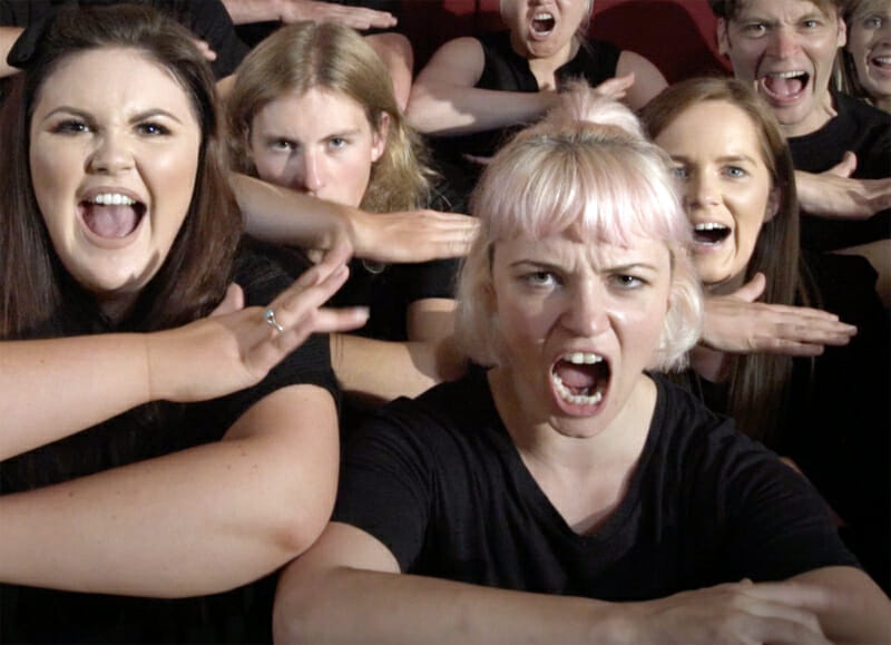 A group of delegates doing the Haka and making serious facial expressions during their corporate away day with Orangeworks.