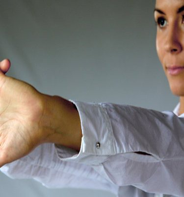 A lady stretching with her palms facing out, participating in Head to Toe, a mindfulness activity.