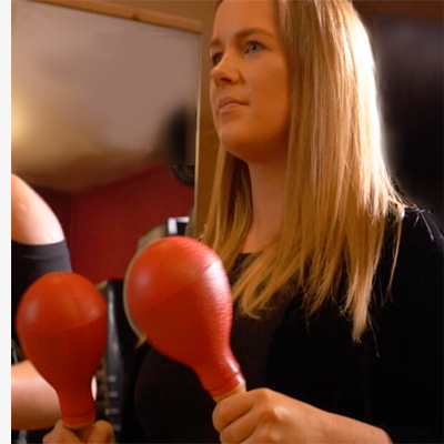 Participant of the corporate team building event Re-Percussion, shaking red maracas.