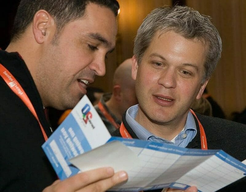 Two delegates looking at their question cards to see if they have anything in common with one another during the Orangeworks icebreaker event.