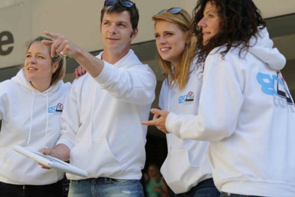 Team wearing white hoodies and pointing to where they will go next during their treasure hunt team building challenge.