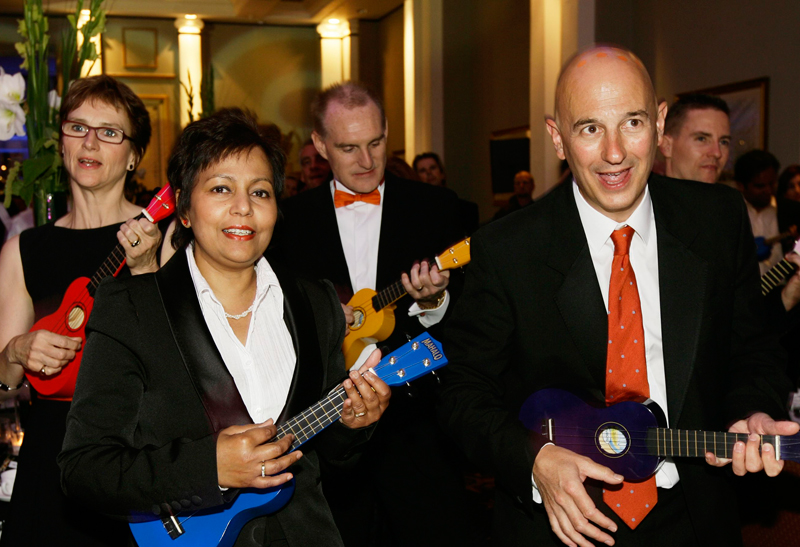 Five participants of the conference energiser, Uke Can Do It, smiling while holding ukuleles as they enjoy learning how to play them.