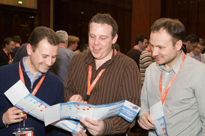 Three men reading the question card and chatting about their interests during Orangeworks icebreaker event called Knowing Me Knowing You.