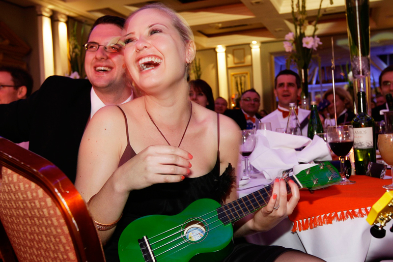 A lady, of the team-building exercise Uke Can Do It, laughing as she and her acquaintances sit at a table and learn how to play the ukulele.