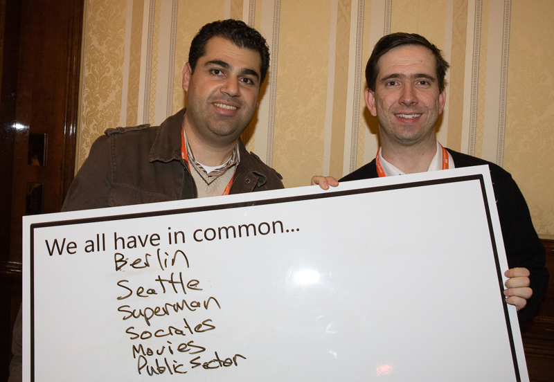 Delegates holding up a whiteboard with things they have in common during Knowing Me Knowing You, an icebreaker activity by Orangeworks.