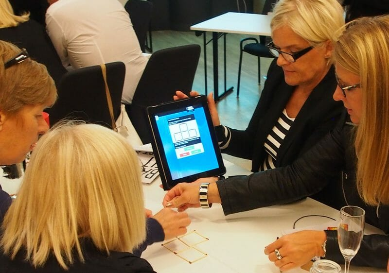 A team discussing a Quickfire challenge on their iPad during their corporate evening event with Orangeworks.