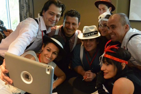 Happy team in 1920's dress smile for group selfie, during Orangeworks escape room style team building activity.