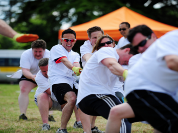 Delegates wearing white tshirts pulling a rope during Tug of War, one of the team challenges completed during Two Tribes.