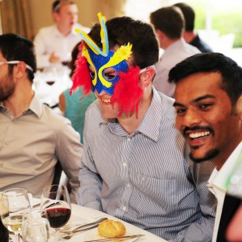 Delegates smiling wearing their masks in one of our role play team building games