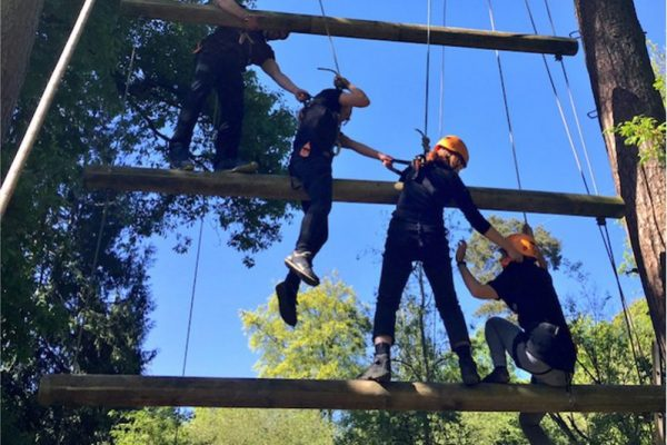 Delegates helping each other climb the jacobs ladder at Orangeworks adventure zone.