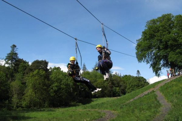 Two delegates on the zip line at Orangeworks adventure zone.