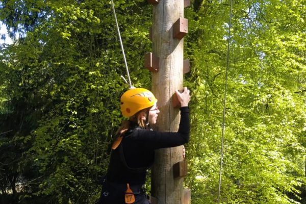 A delegate climbing up the Jacobs Ladder wearing a yellow helmet, at the Orangeworks adventure course.