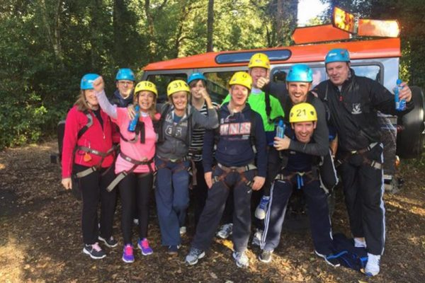 Delegates wearing helmets smiling as they have completed their high ropes course with Orangeworks.