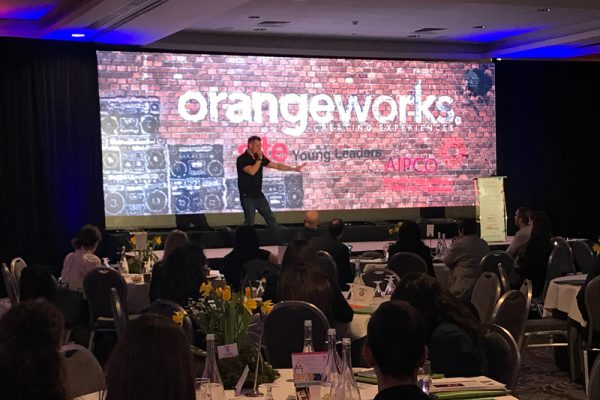 Dean, Orangeworks Beatboxer, on stage at an AIPCO conference, getting the crowd ready for their beatboxing icebreaker energiser.