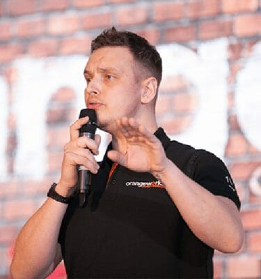 Dean, an Orangeworks Beatboxer, standing on stage at a team-building event teaching participants how to beatbox.