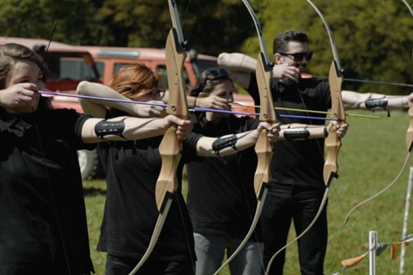 Team holding their bow and arrows taking part in some archery with Orangeworks.