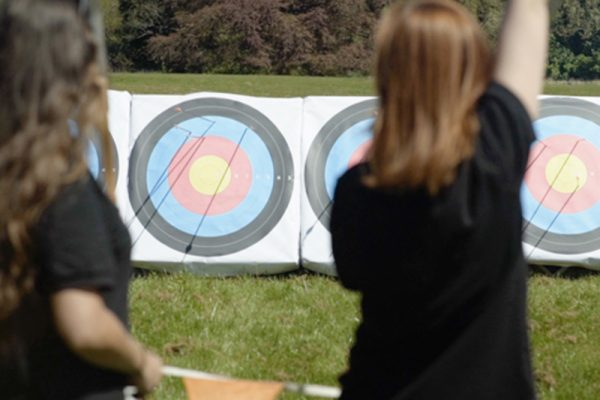 Delegates cheering after hitting a bulls eye in Archery, an outdoor adventure activity with Orangeworks,