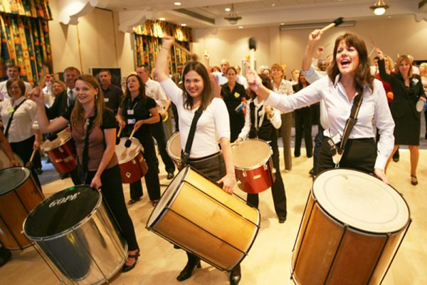 Participants of the team building activity Beatswork, smiling, dancing and playing the drums at their conference event.