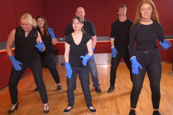 A team wearing blue gloves performing their musical clapping sequence during Body Rap, a musical team building activity.
