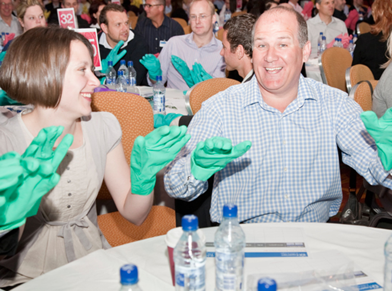 Smiling delegates wearing green gloves and making music with them during Body Rap, an Orangeworks musical team building event