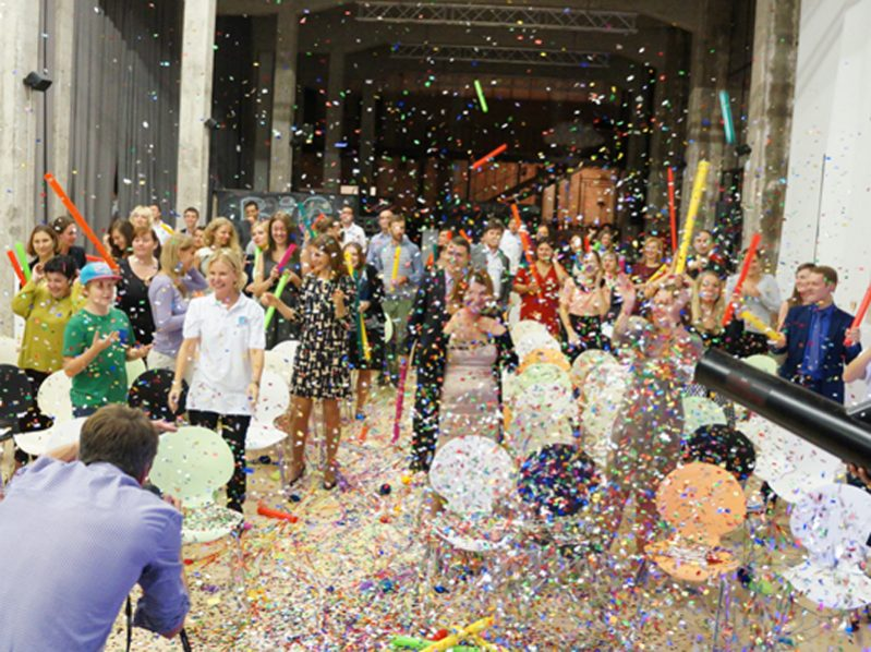 Participants celebrating the finale of Boom Time, an icebreaker event by Orangeworks, making music with Boom whackers surrounded by confetti.