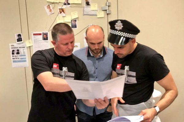 Delegates looking at evidence as they try to solve the crime during the team building activity by Orangeworks.