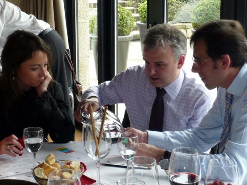Delegates pouring wine at their table in Calling the Shots team building event